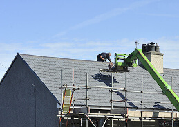 man installing new roofing onto home